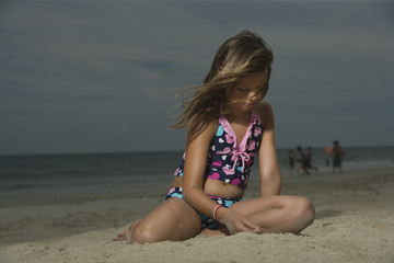 Sad Little Girl Sitting on a Beach