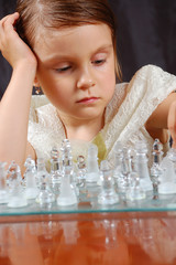 thoughtful little girl playing  glass chess