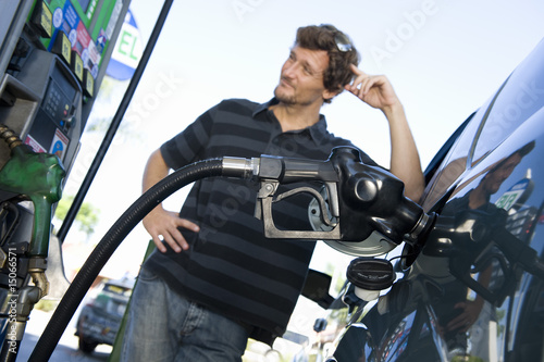Smiling man refueling car at natural gas station