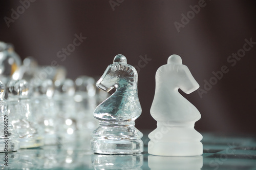 two glass knights on chessboard against black background