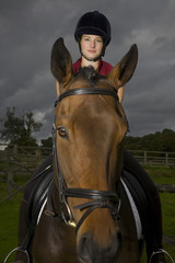 Female horseback rider sitting on brown horse, portrait
