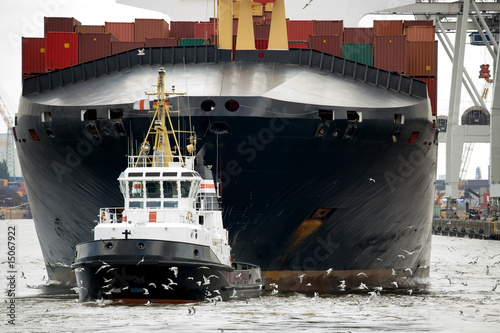 tugboat towing freighter in harbor - 15067922