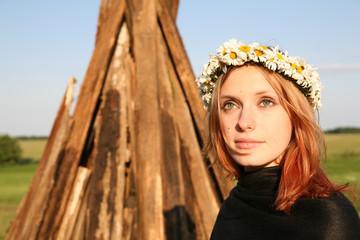 Redheaded woman with diadem near bonfire