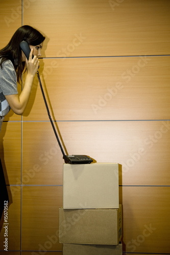 Office worker on telephone on cardboard boxes in office