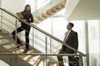 Businesswoman and businessman on office staircase