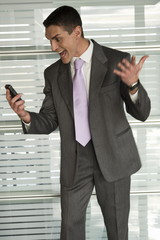 Businessman in office shouting at cell phone