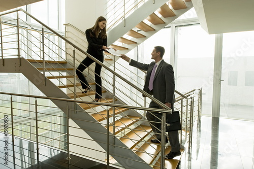 Businesswoman and businessman exchanging document on office staircase
