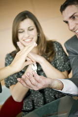 Couple receiving keys from female hand
