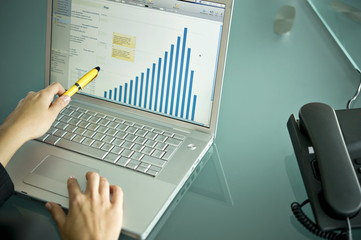 Businesswoman's hands with laptop showing bar chart