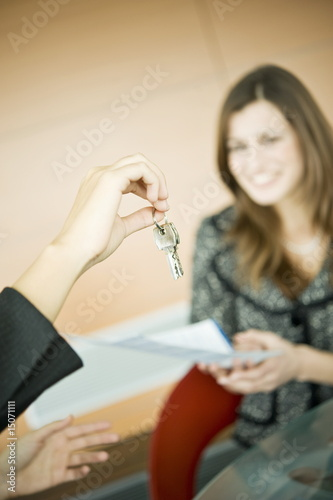 Young woman holding document, female hand holding keys