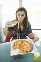 Businesswoman eating pizza at desk