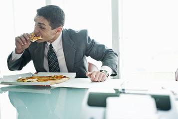 Businessman eating pizza at desk
