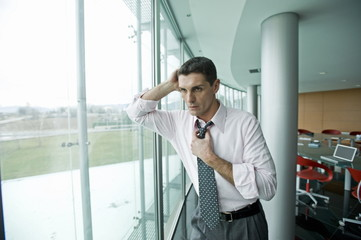 Businessman looking out the window, adjusting tie