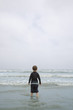 Young Boy Standing in Surf