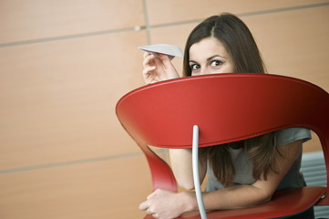 Businesswoman hiding behind chair with paper airplane