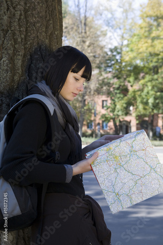 Young woman study map leaning on tree
