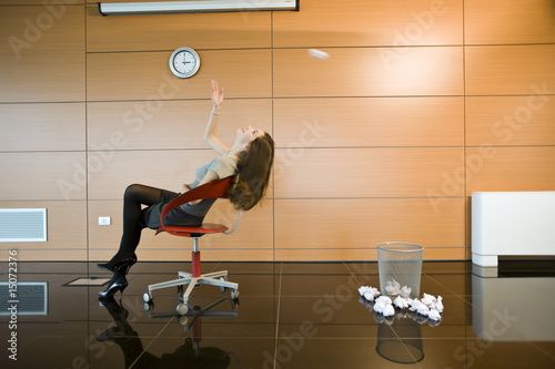 Businesswoman throwing paper into basket