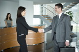 Businessman and businesswoman shaking hands at reception