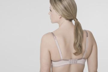 Young woman wearing bra, rear view