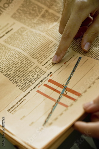 Hands holding newspaper with chart analyzing financial crisis