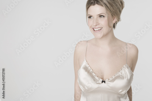 Pretty young woman wearing sexy nightshirt, smiling