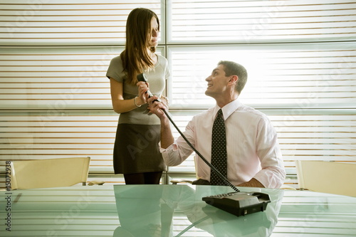 Businessman giving the phone to businesswoman