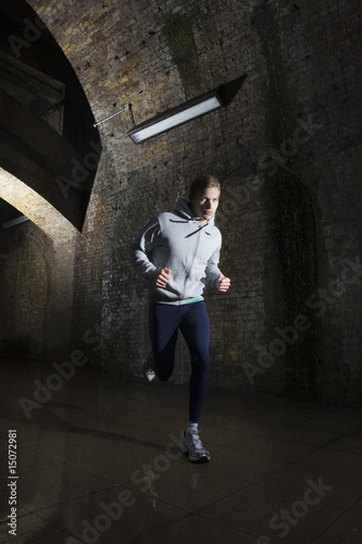 Young man jogging through urban tunnel at night