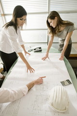 Professionals looking at architectural plans on desk