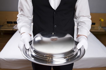 Torso of waiter holding covered silver platter