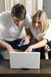 Young couple at laptop computer with credit card