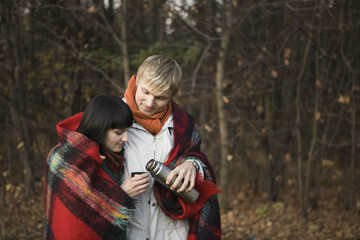Young couple wrapped in blanket, embracing in forest