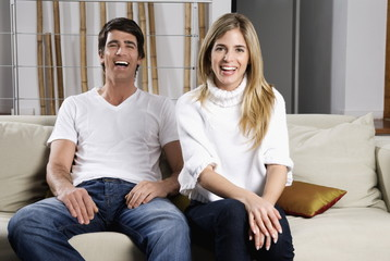 Young couple on couch laughing