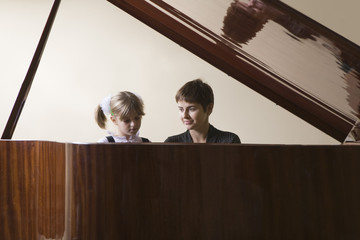 Female student 5-6 and teacher playing piano