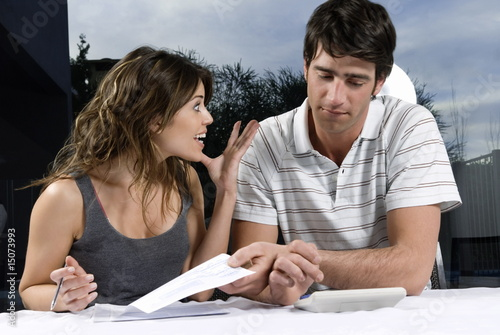 Young couple with check and calculator