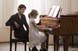 Girl 5-6 playing piano accompanied by teacher