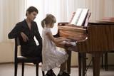 Girl 5-6 playing piano accompanied by teacher