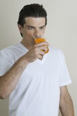 Young man drinking a glass of juice