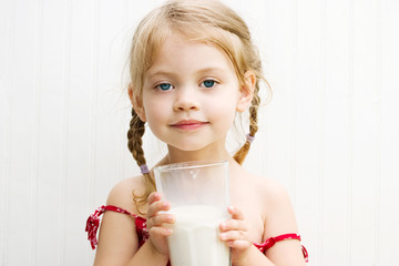Child drinking a large glass of milk with a milk mustache