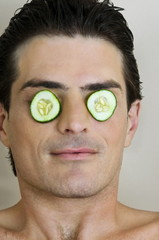 Young man with cucumber slices on his eyes