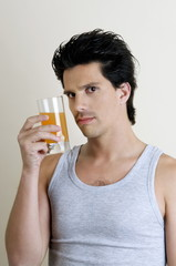 Young man holding a glass of juice