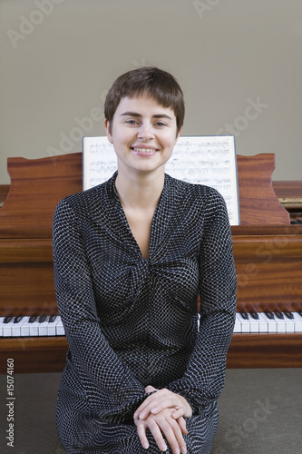 Portrait of woman sitting in front of piano