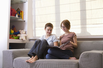 Two teenage girls looking at photo album on sofa