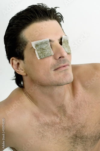 Young man with tea bags on his eyes