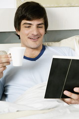 Young man in bed with book and coffee cup