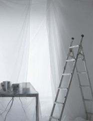 Desk with phones and cables covered in transparent dust sheets with step ladder