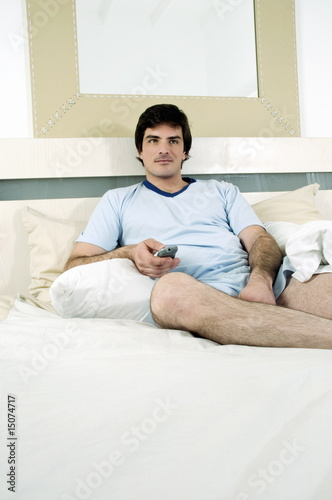Young man in bed with remote control