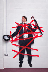 Businessman stuck to wall with red tape