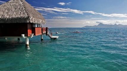 Men on kayaks next to over water bungalow
