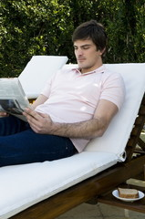 Young man on chaise lounge reading