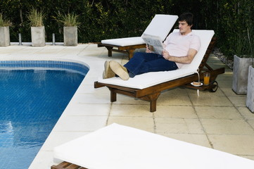 Young man on chaise lounge by pool reading